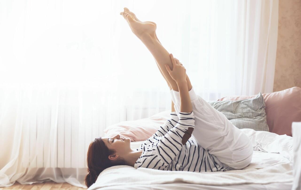 Kvinna som stretchar benen i sängen