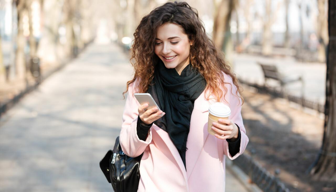 Kvinna på gata tittar i telefonen.