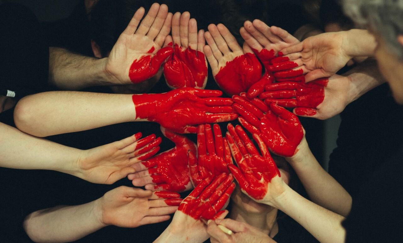 Händer målade med röd färg formar ett hjärta.