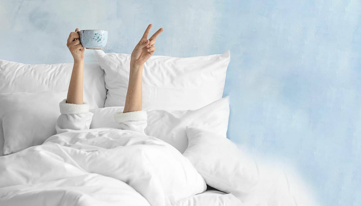 Kvinna ligger ensam i en säng och gör segertecken med ena handen.