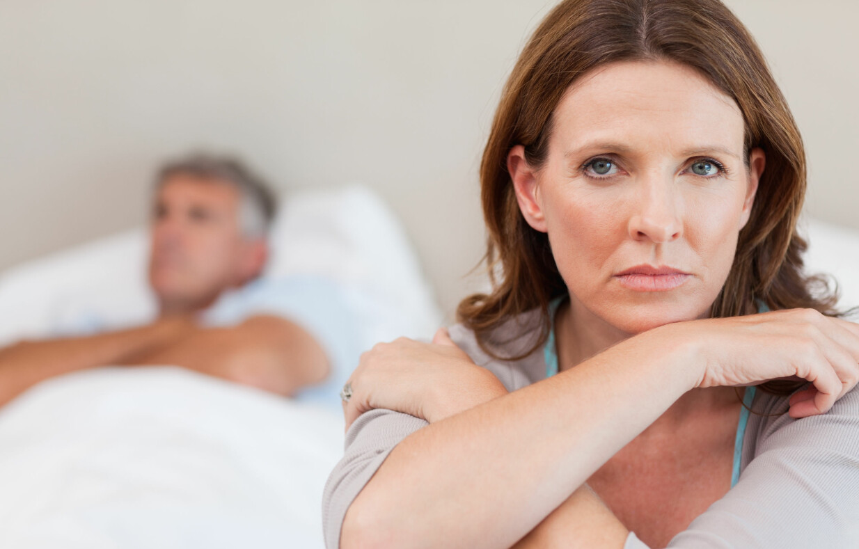 Kvinna sitter i säng och ser ledsen ut. I Bakgrunden syns en besviken man.