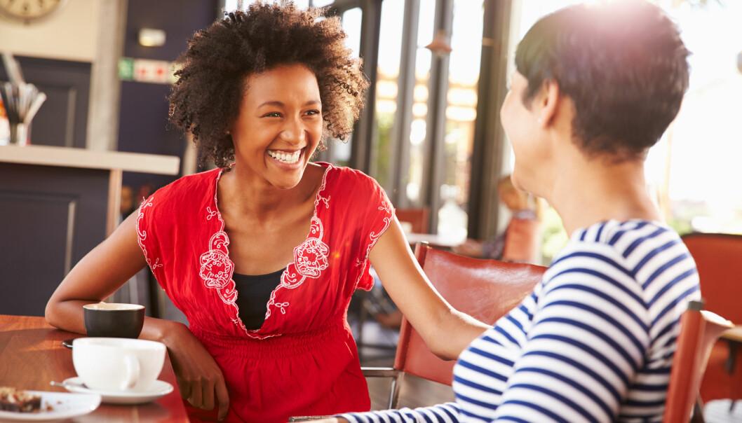 Tva vaninnor som sitter pa ett kafé i solsken och pratar.