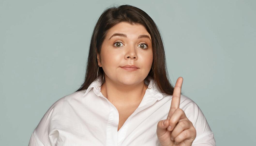 Kvinna som haller upp sitt pekfinger och tillbakavisar nagon.