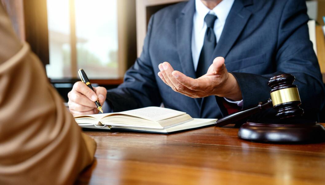 Advokat sitter bakom skrivbord med klubba.