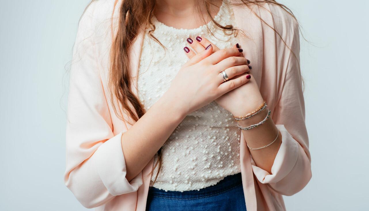 Kvinna håller händerna för bröstet.