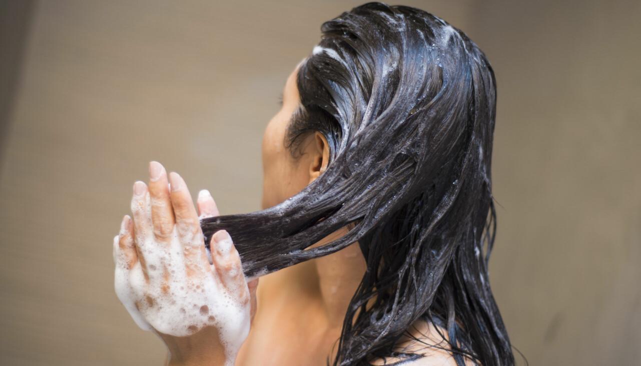 Kvinna tvättar håret med balsam.
