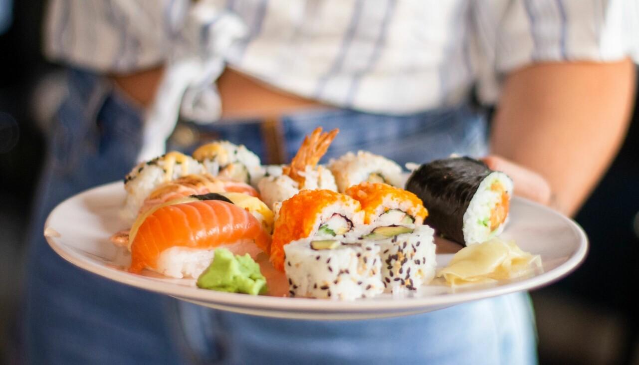 Kvinna håller fram ett fat med färsk sushi.