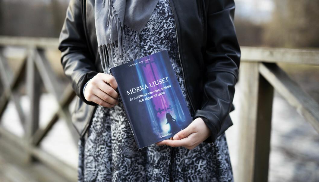 Zahra visar upp sin roman Mörka ljuset.