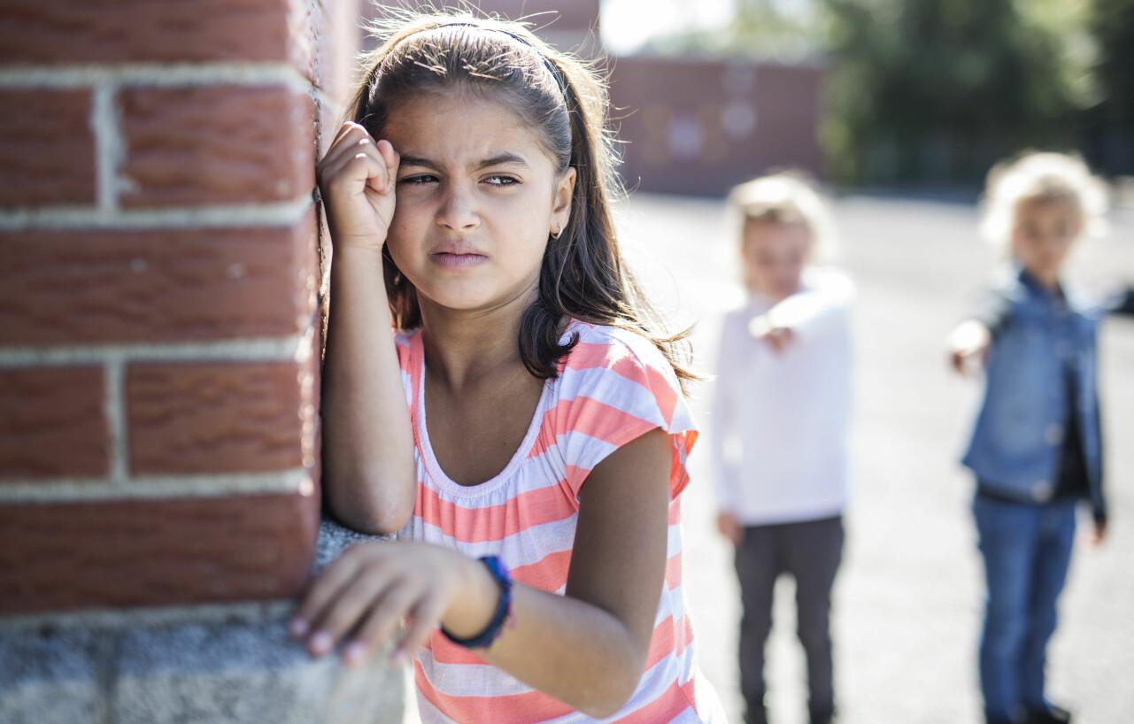 Liten flicka på skolgård ser ledsen ut.