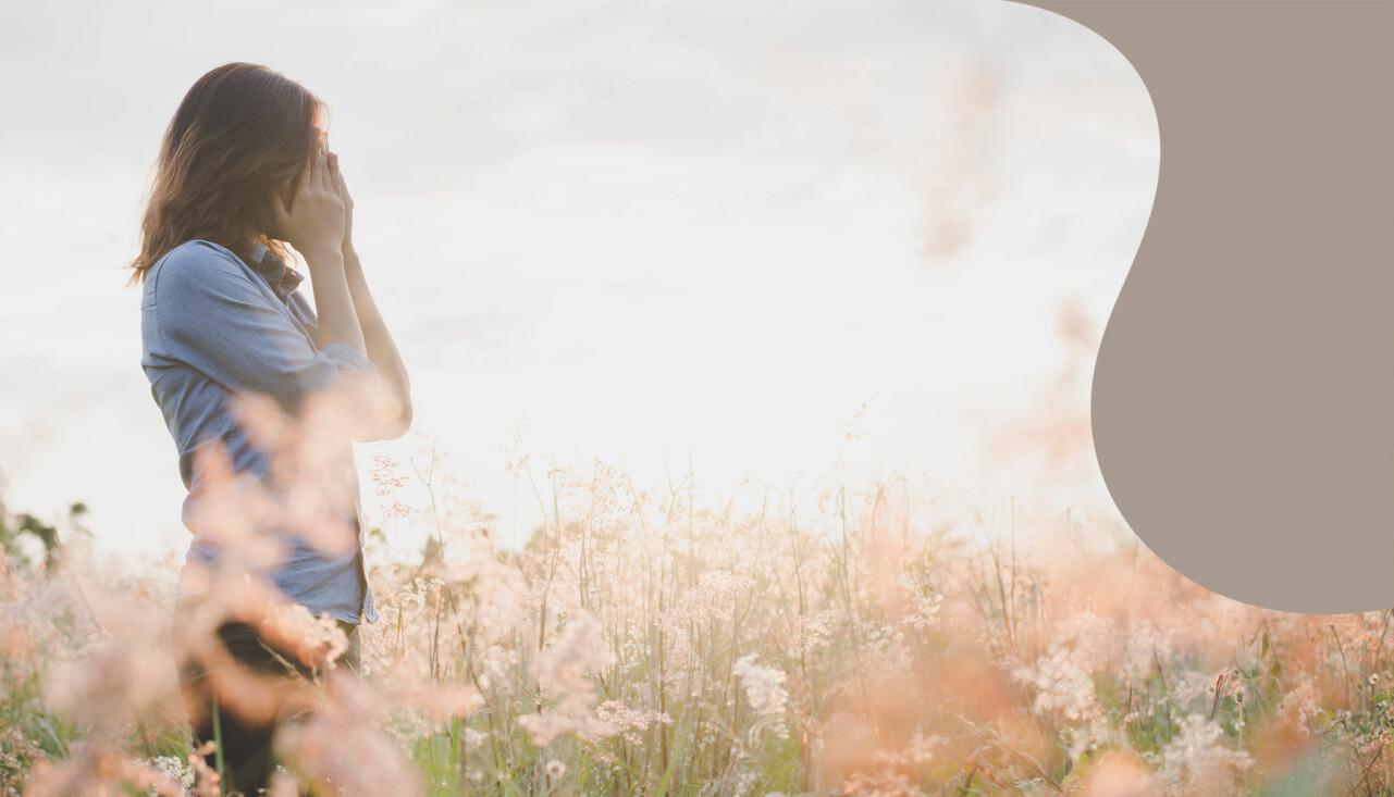 Ledsen kvinna står på en äng och håller händerna för ansiktet.