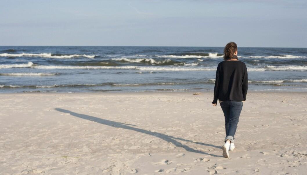 Kvinna går på strand och njuter av frihet och lugn.