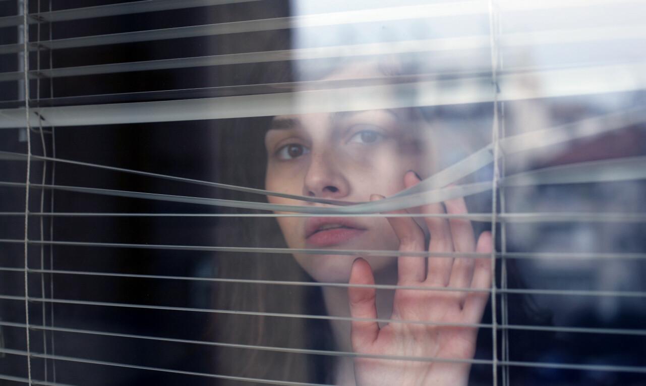 Rädd kvinna tittar ut genom persiennerna på ett fönster.