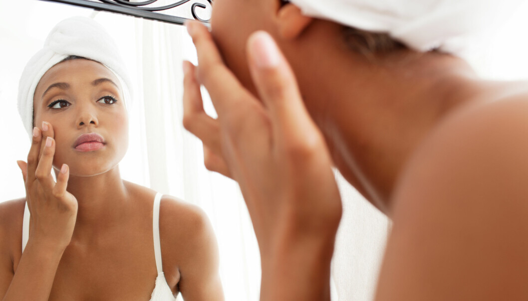 Kvinna rengör sitt ansikte framför spegeln.