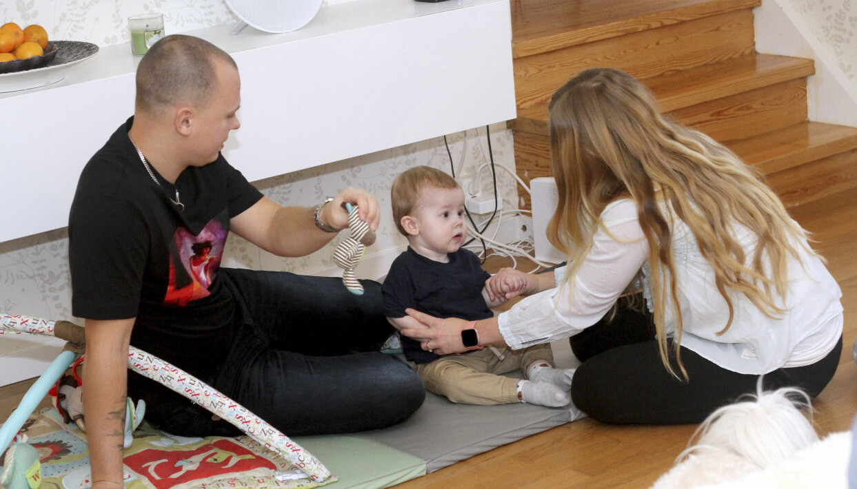 Tom, Linda och Elton sitter på en mjuk matta i familjens vardagsrum och leker.