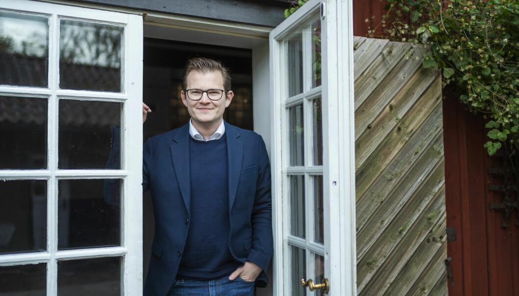 Jakob, 29 år och deltagare i Gift vid första ögonkastet 2020, står framför en glasdörr.