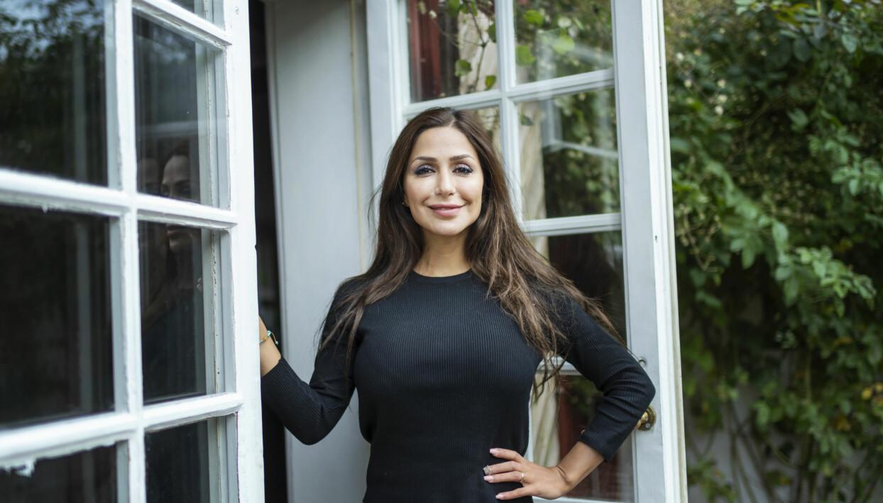 Elaine, 28 år och deltagare i Gift vid första ögonkastet 2020 står framför en glasdörr.
