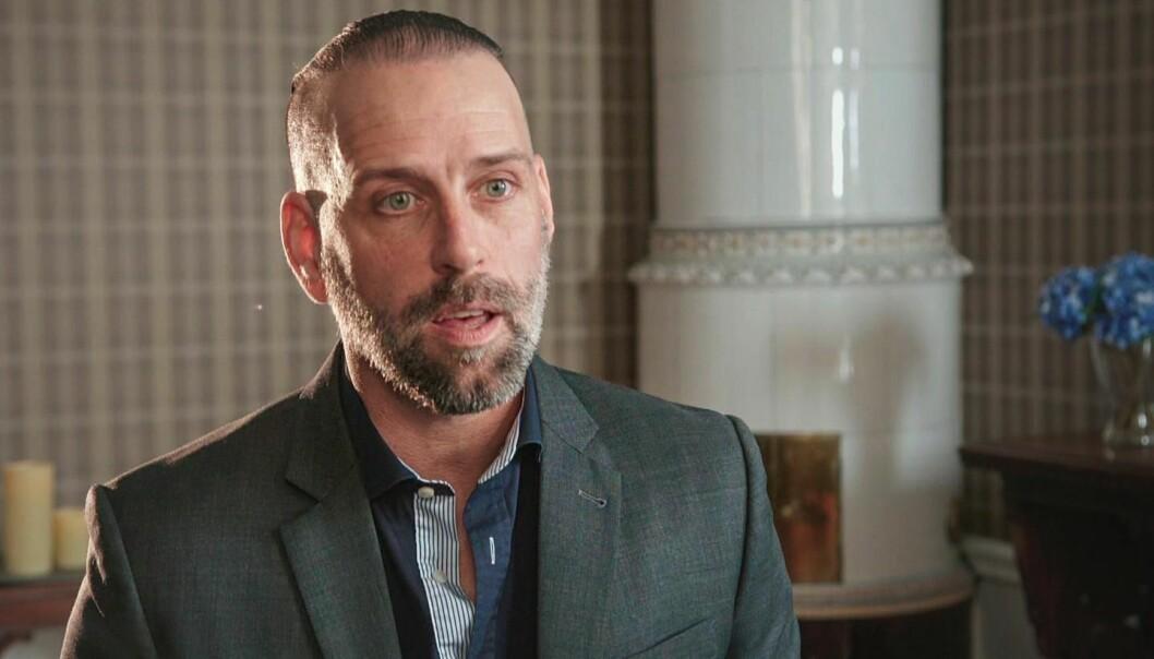 Fredric Bohm, psykolog i Gift vid första ögonkastet på SVT sitter framför en kakelugn.