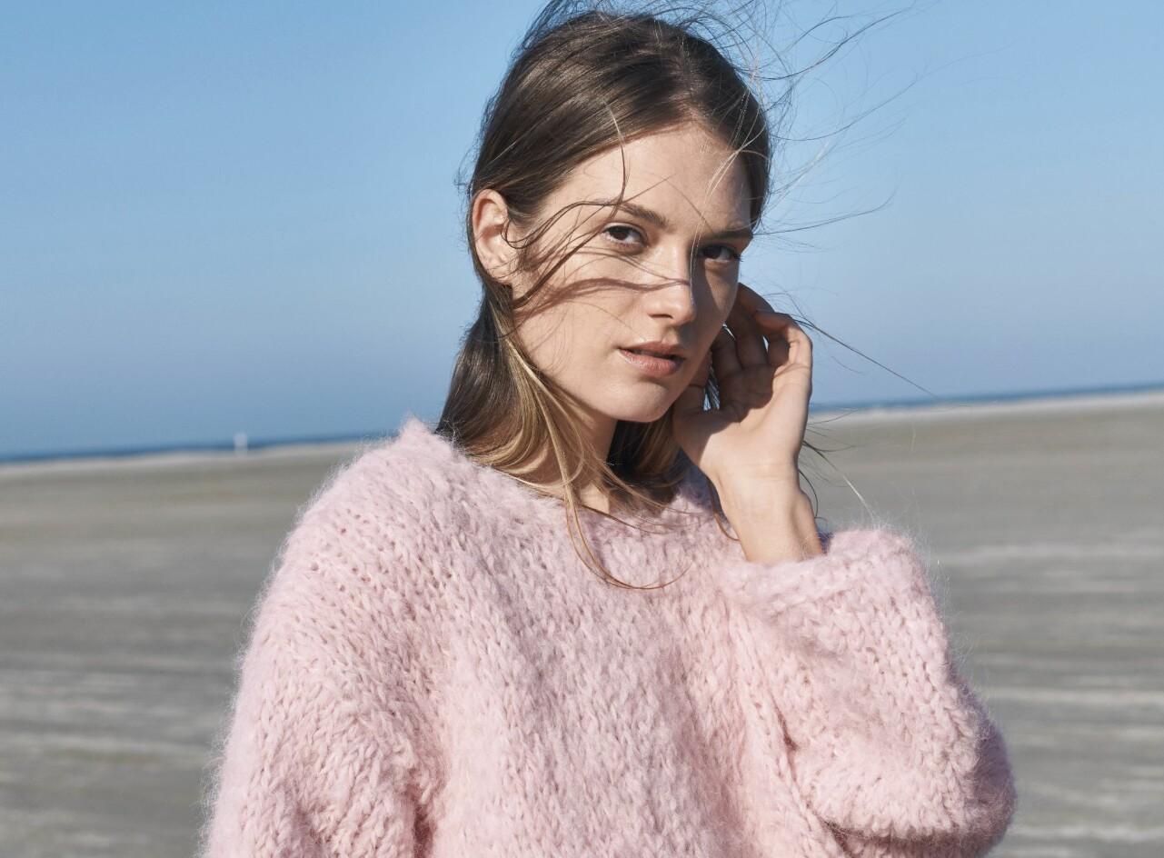 Kvinna i den fluffiga rosa tröjan utomhus.