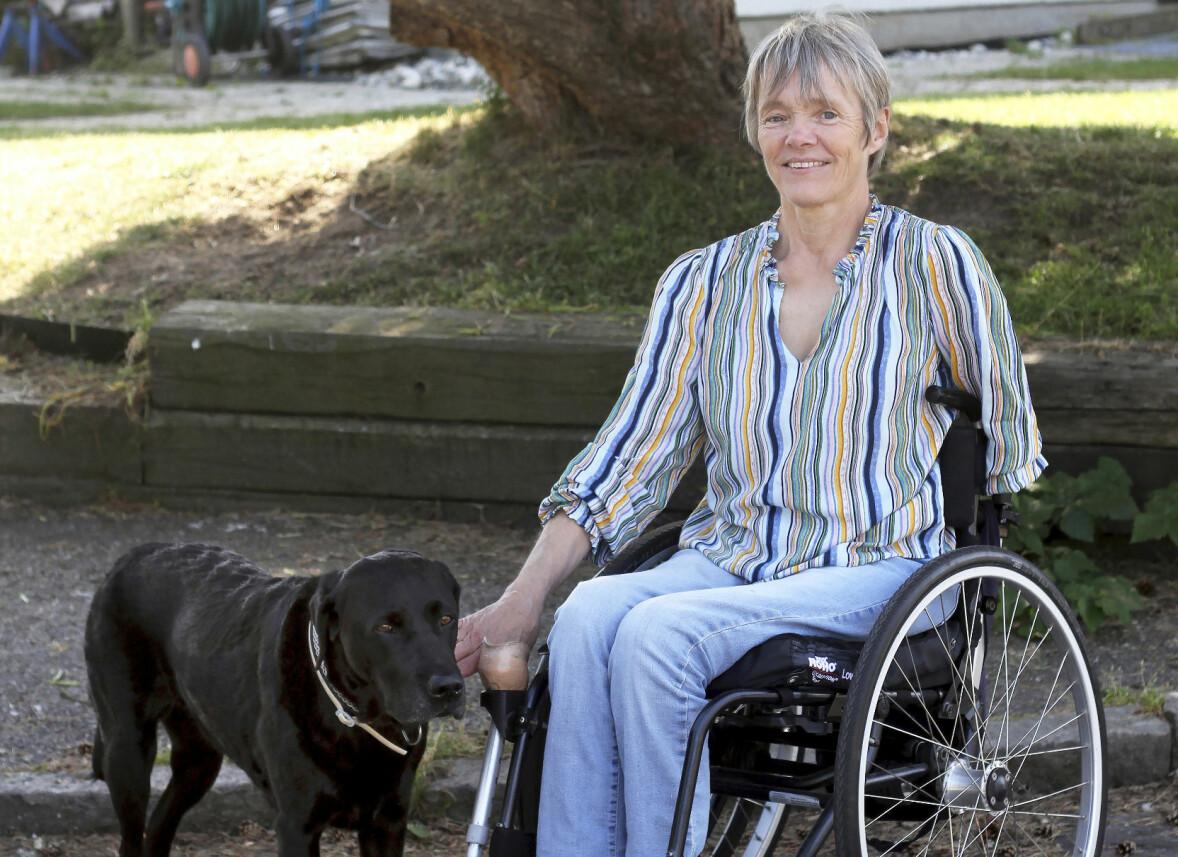 Gunilla sitter i sin rullstol utomhus framför ett träd och har den svarta labradoren och servicehunden Sassa bredvid sig