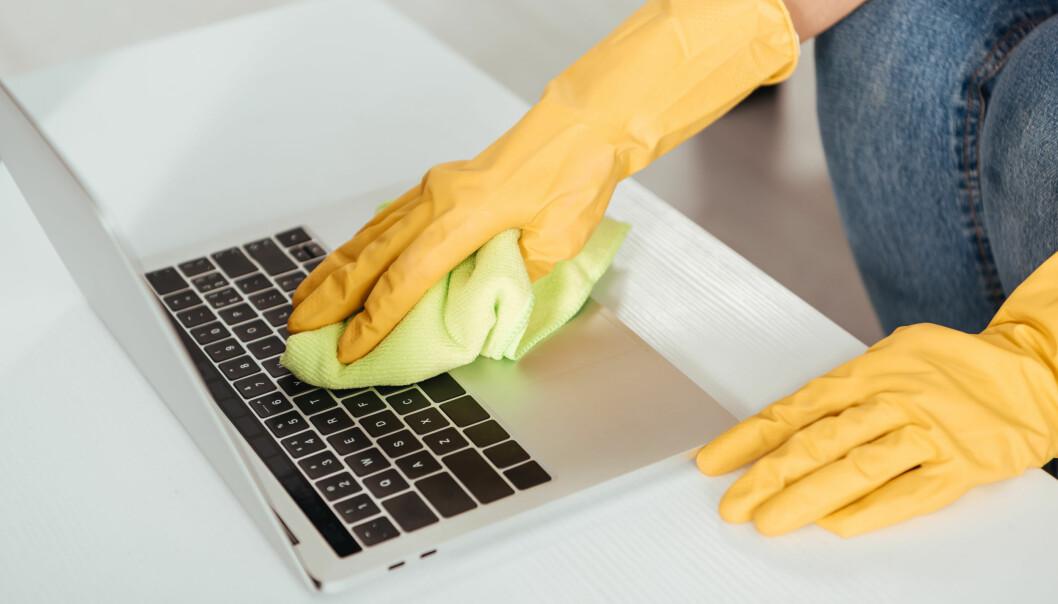 Kvinna rengör sitt tangentbord med en mikrofiberduk.