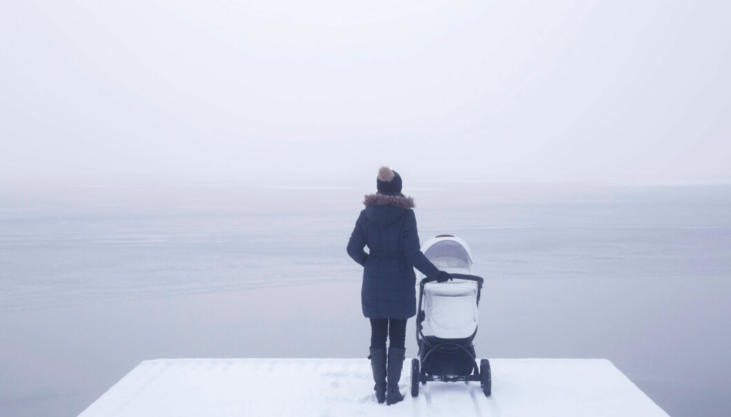 En kvinna med barnvagn står och tittar ut över havet i vintertid.