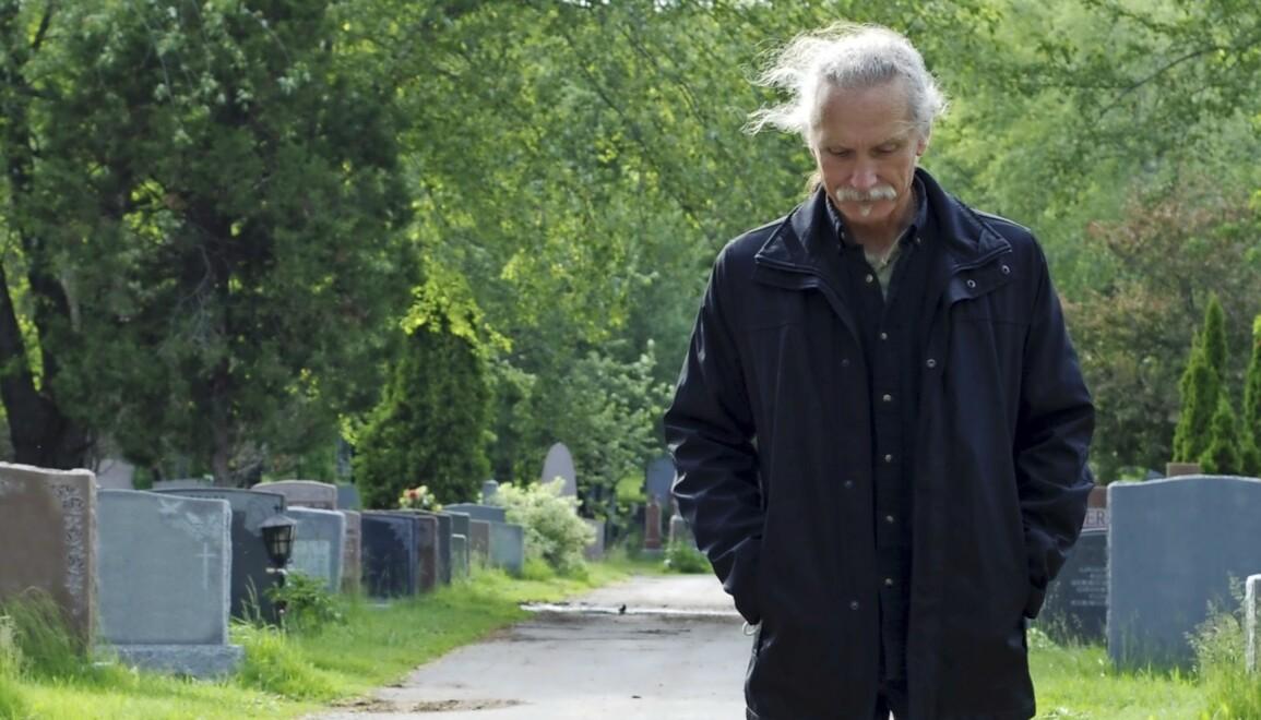 En man går längs en kyrkogård.