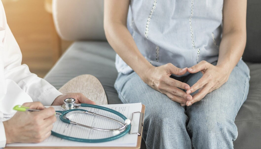Kvinna i ett mottagningsrum med en läkare.