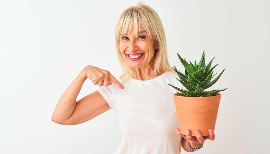 Kvinna håller i en växt i en kruka.