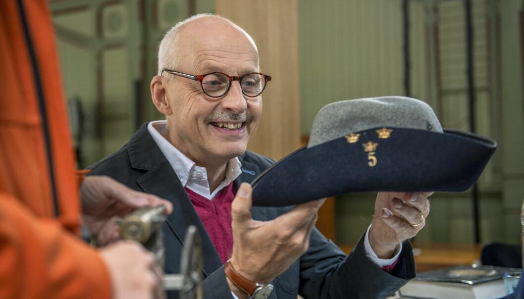 Experten Max Sjöberg studerar en huvudbonad från en gammal uniform.