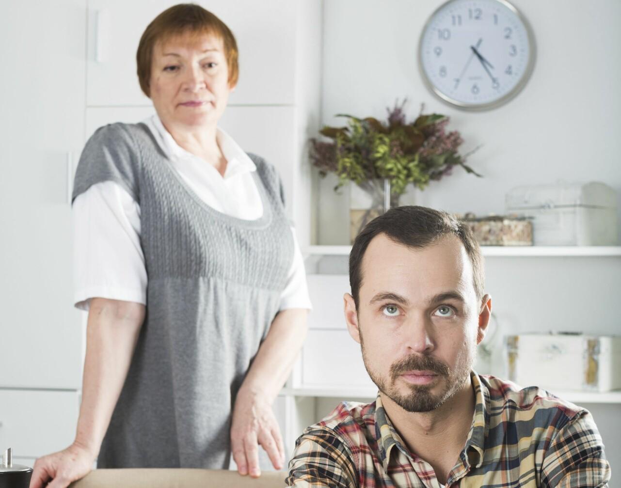 Man sitter vid ett bord och himla mer ögonen åt sin mamma som står bakom honom.