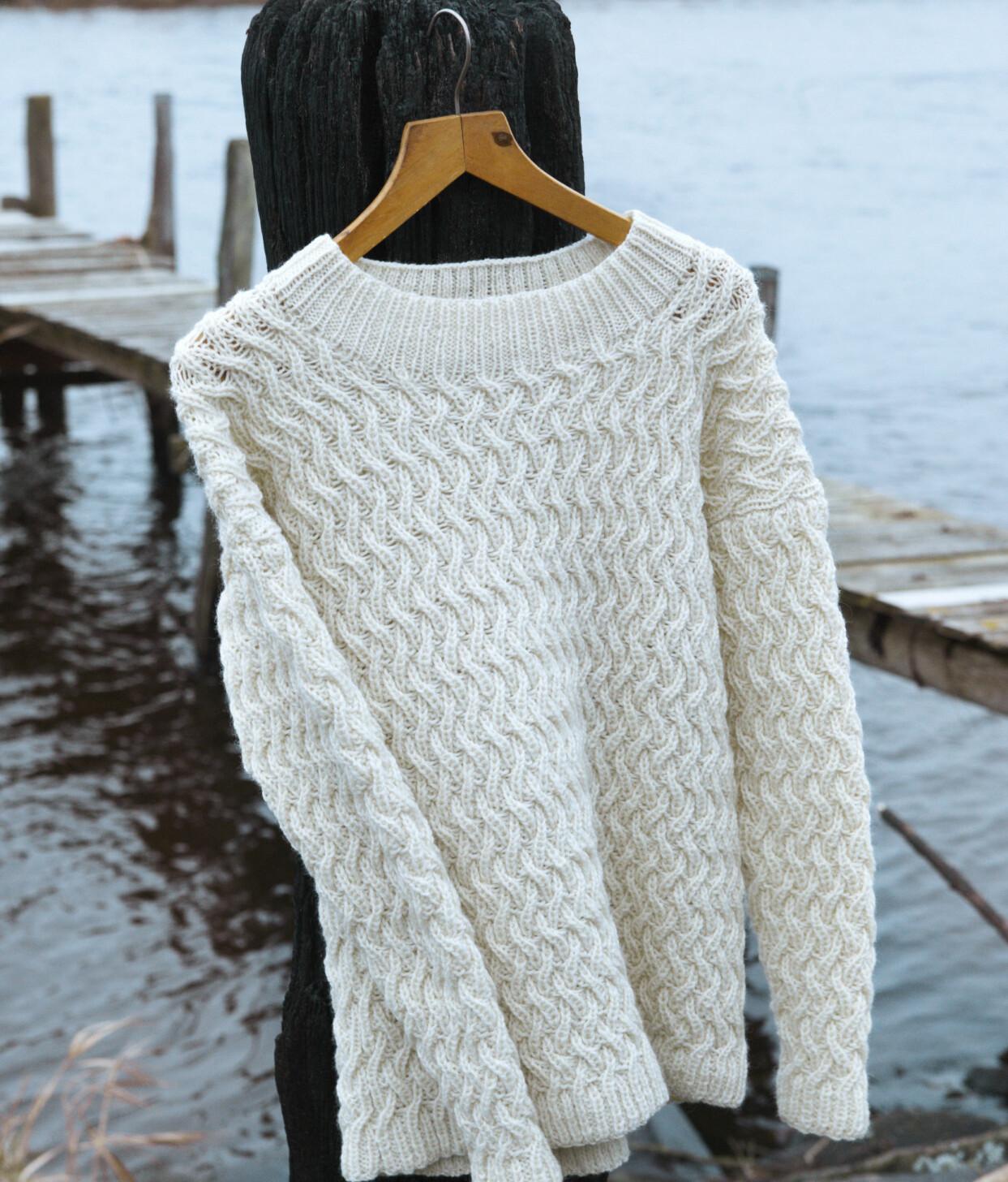 Stickad fiskartröja i ull som hänger på en galge.