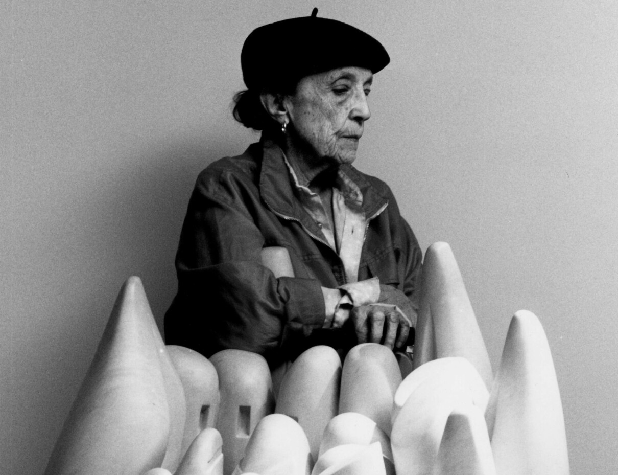 Louise Bourgeois poserar framför en skulptur.