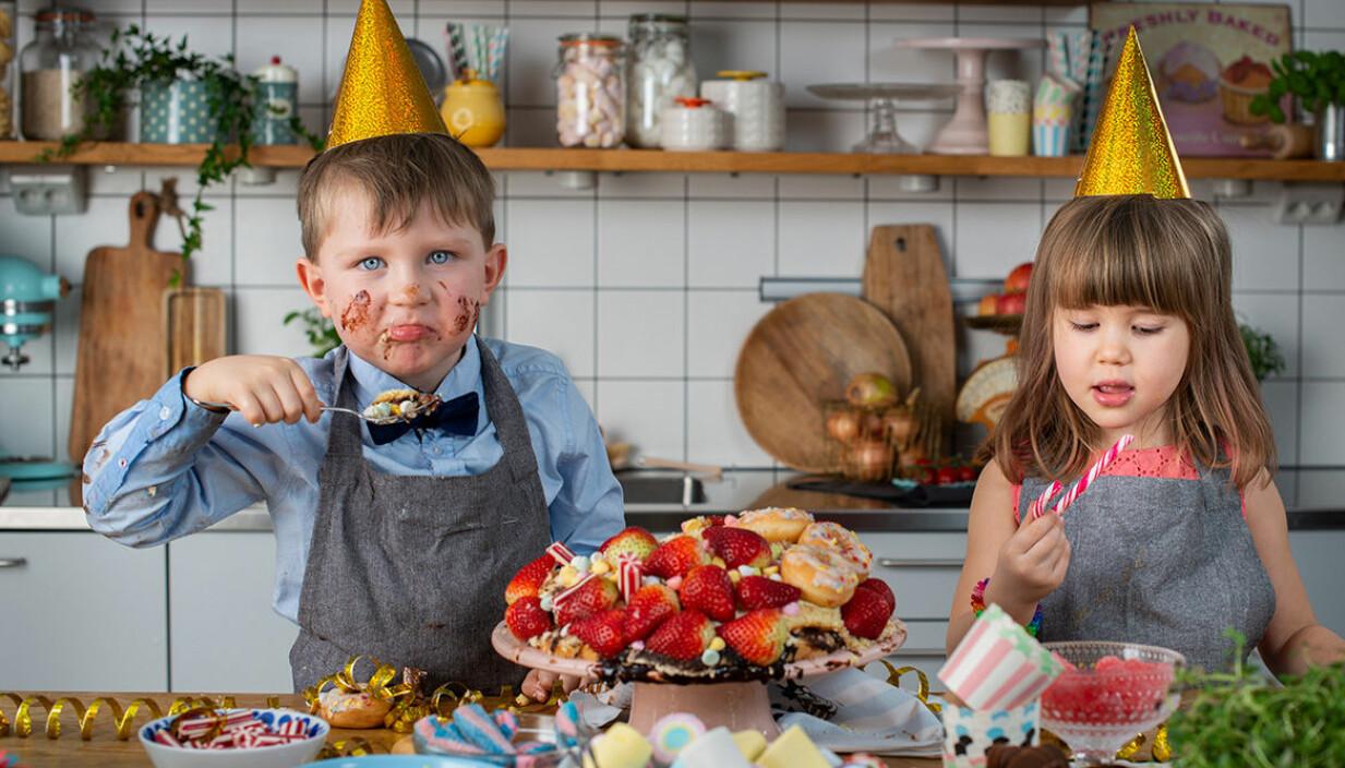 Två barn äter tårta på kalas.
