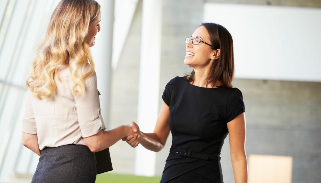Två kvinnor skakar hand.