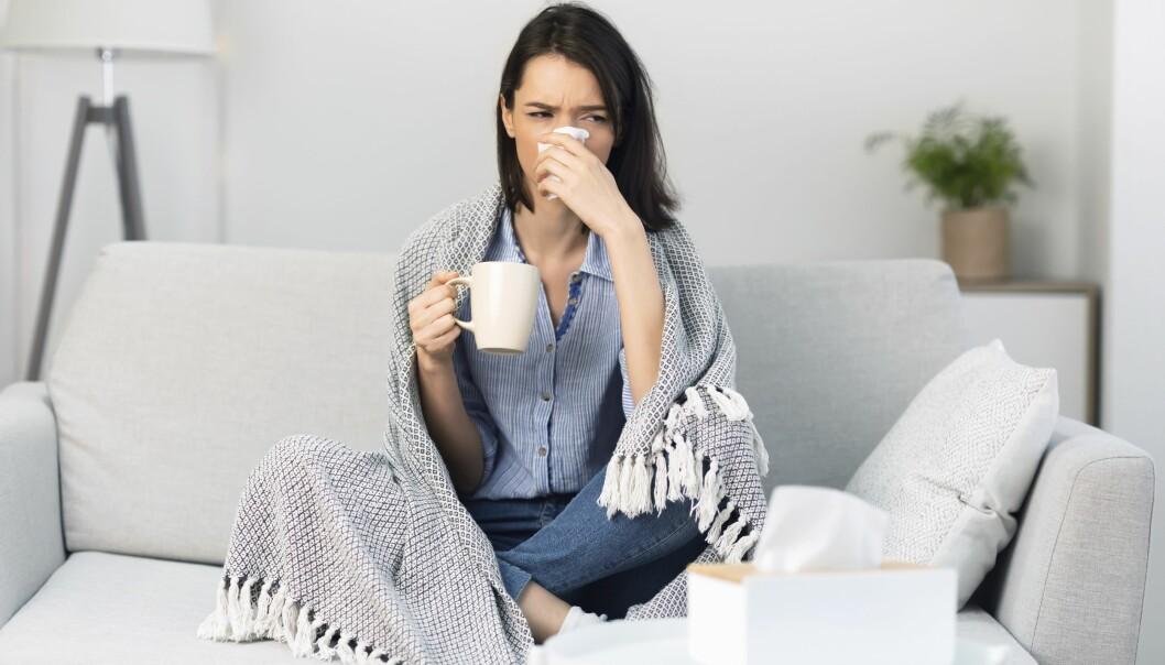 Kvinna som sitter i en soffa och snyter sig