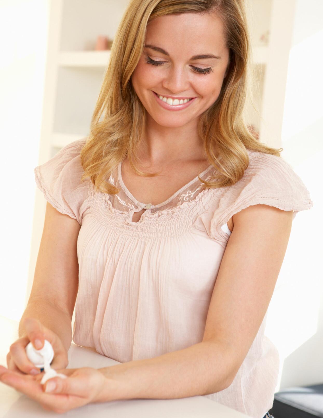 En kvinna tvättar händerna med handsprit.