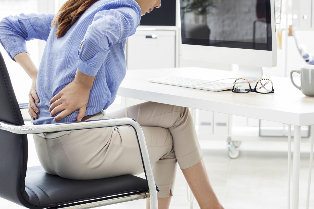 En kvinna med smärta i ryggen tar sig för den nedre ryggen.