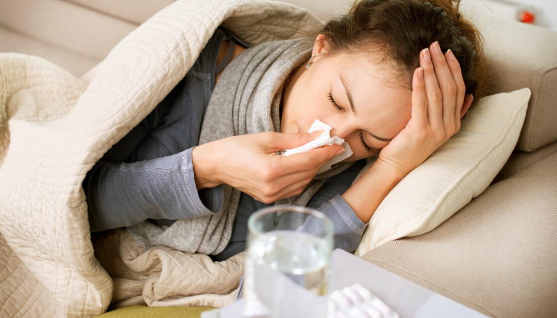 En kvinna ligger i soffan med influensasymtom.
