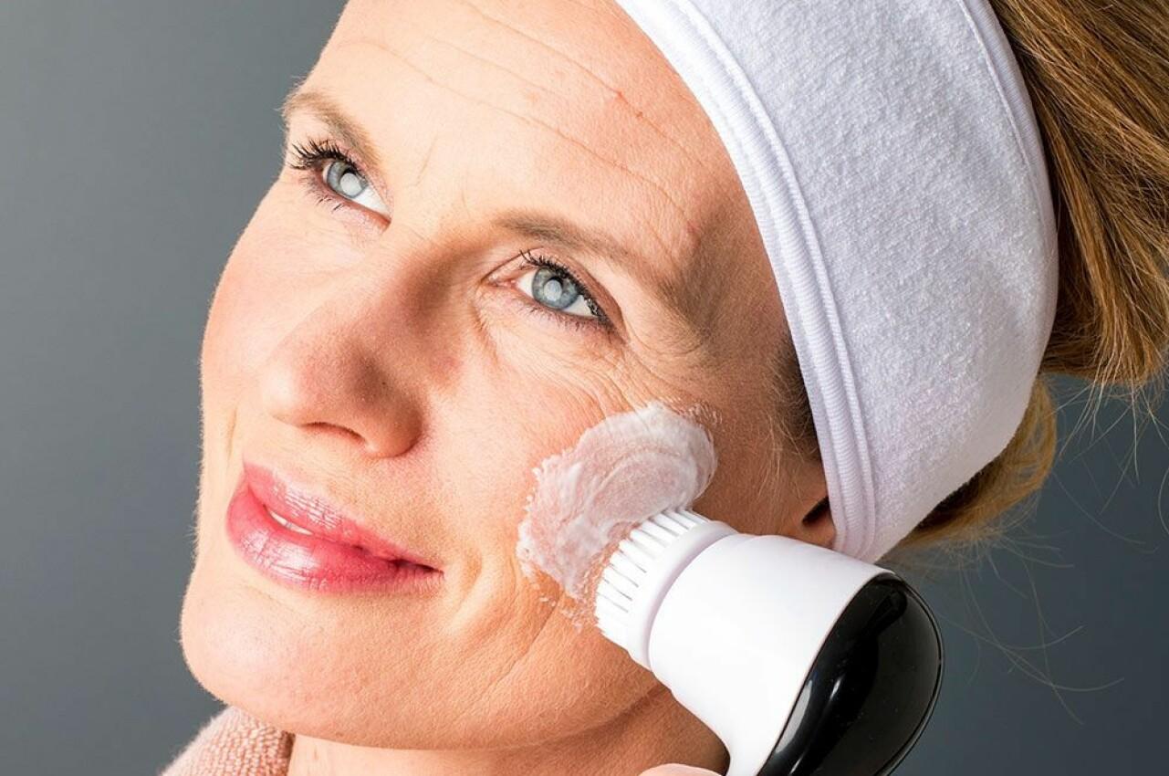Kvinna använder en ansiktsborste.