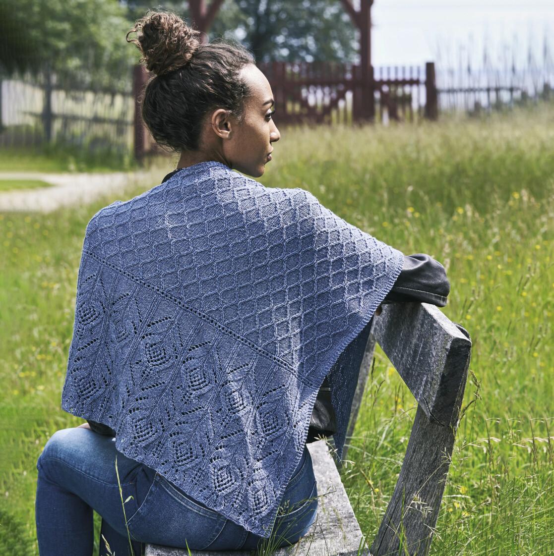 Kvinna sitter på en bänk iklädd en stickad sjal med fint mönster och vacker lila färg.