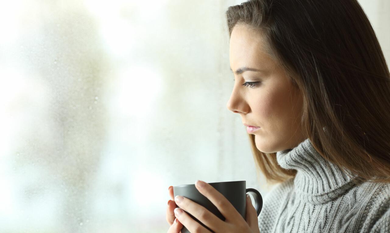 Kvinna tittar ut genom ett fönster.