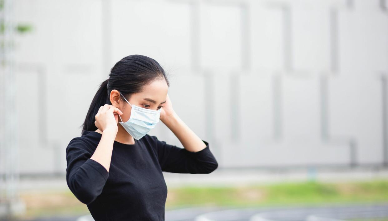 Kvinna i svart tröja rättar till sitt munskydd.