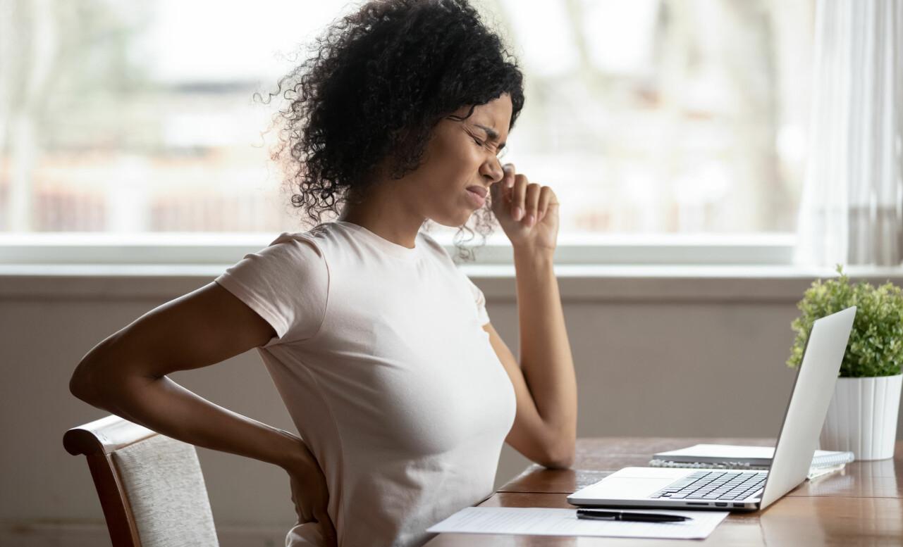 Kvinna sitter vid en dator och håller sig för ryggen av smärta.