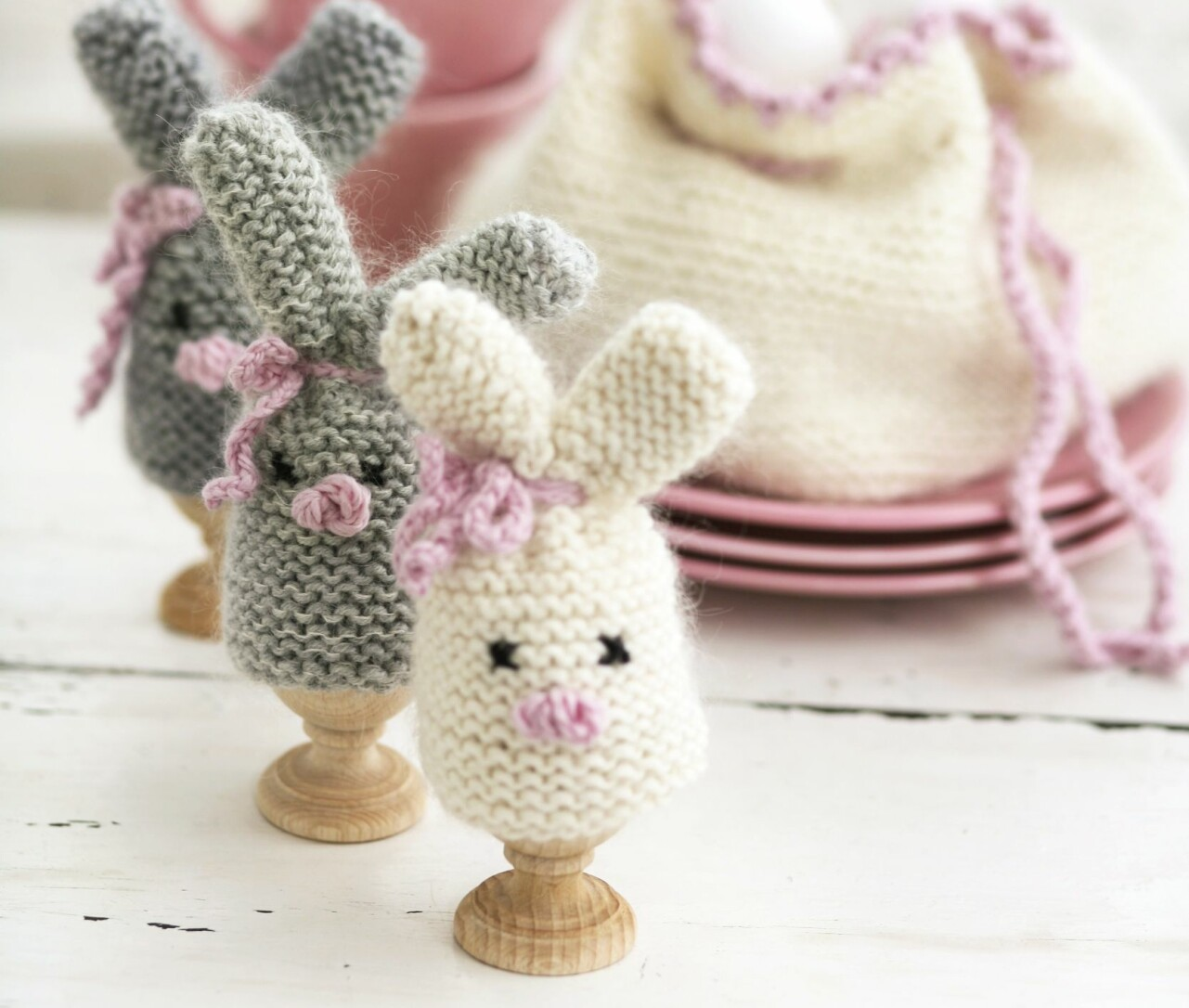 Grå och vita äggvärmare i form av stickade påskharar, design Drops Design/Garnstudio