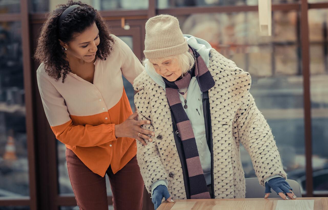 Ung kvinna hjälper äldre kvinna.