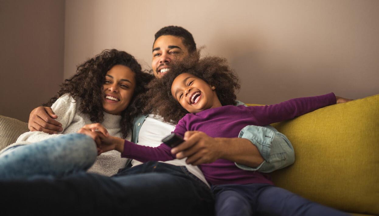 Familj sitter tillsammans i en soffa och tittar på tv.