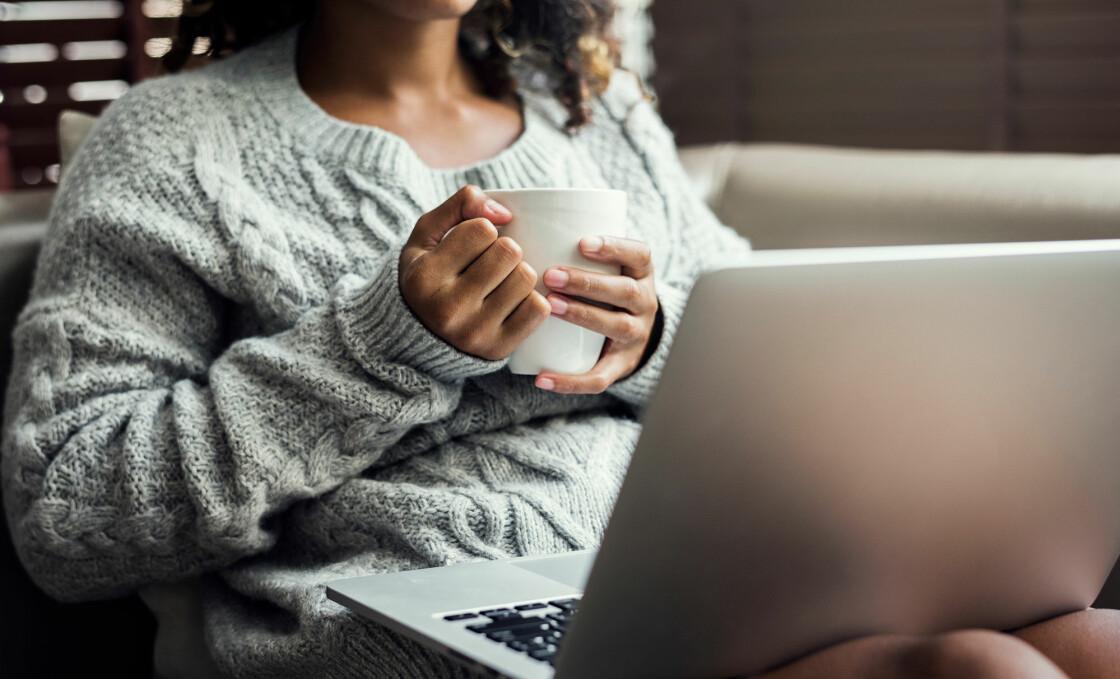 Kvinna sitter med en dator i knät.