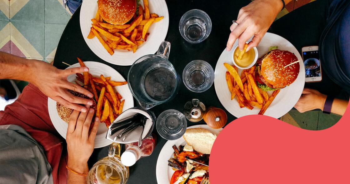 En grupp människor äter hamburgare på restaurang.