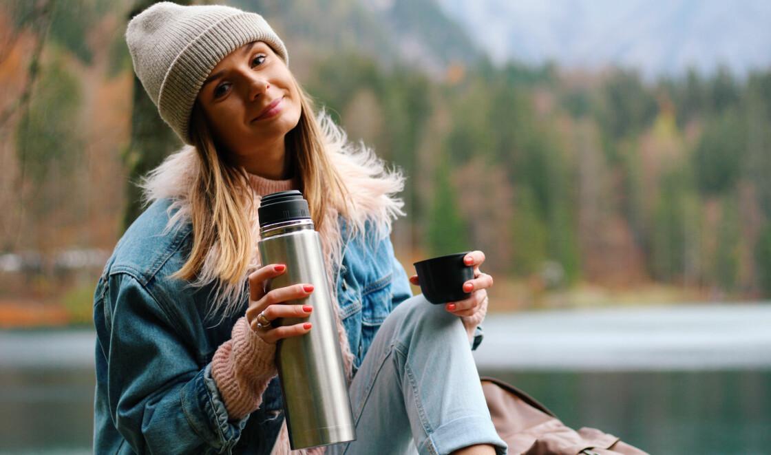 Kvinns dricker kaffe ur termos ute i naturen.
