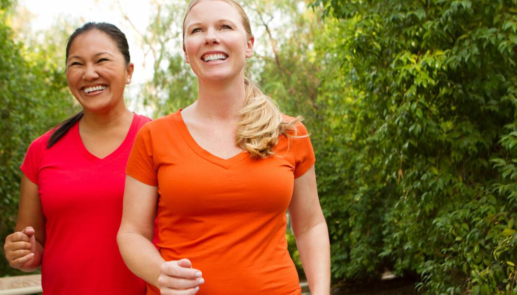 Två leende kvinnor powerwalkar.